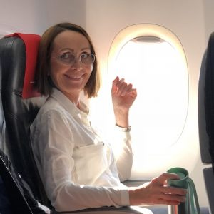 A woman smiling in an airplane seat