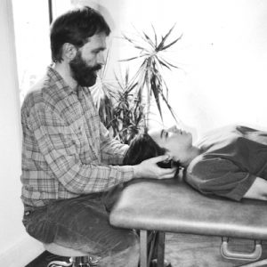 Alan Sheets doing physical therapy for a woman lying down