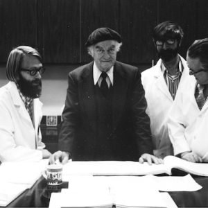 Alan Sheets standing with Linus Pauling and 2 men in lab coats