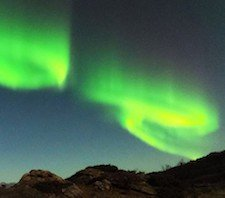 Green Northern Lights swirling over mountains