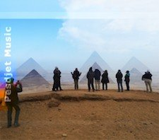 A group of people standing in front of three pyramids in Egypt