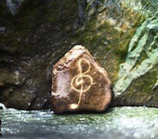 A pentagon shaped rock with a treble clef on it