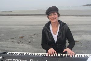 Siv Roland playing a keyboard on the beach