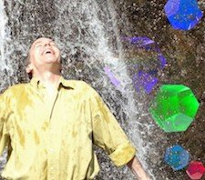 A joyful man under a waterfall with jewels next to him