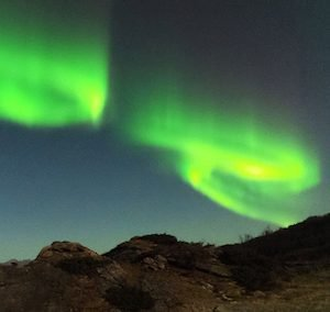 Green swirling Northern Lights over mountains