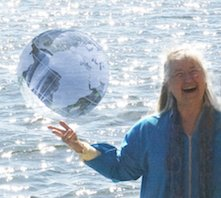 A woman smiling holding a transparent globe in front of the ocean