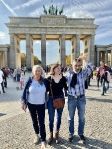 Three people smiling in front of the Brandenburger Tor