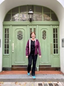 Siv Roland smiling and standing in front of a green door