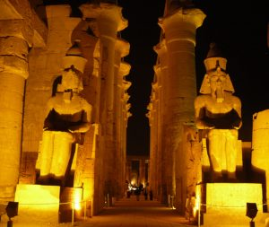 The entrance to the Luxor Temple showing two huge statues in front of huge pillars
