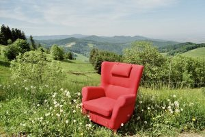 A red arm chair in the grass in front of rolling hills