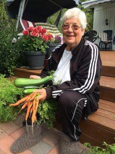 Reidun smiling holding some vegetables she grew