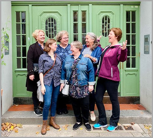 6 women laughing and smiling in front of a green door