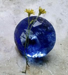 Two tiny yellow flowers on top of a blue crystal