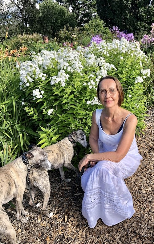 Ingrid wearing a white dress in nature with her two dogs