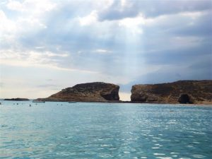 View from the ocean of Gozo Island with the sun shining