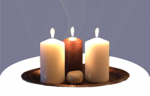 Three burning candles in a metal dish