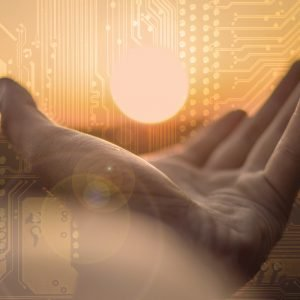 A hand holding the sun superimposed over a microchip