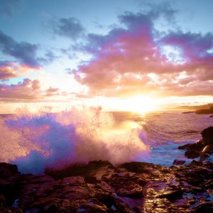 A colorful sunset over crashing ocean waves