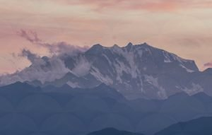 A pink sunset over grey cloudy mountains